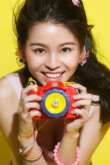 Beautiful stylish young asian woman holding colorful camera and smiling on yellow — Stock Photo