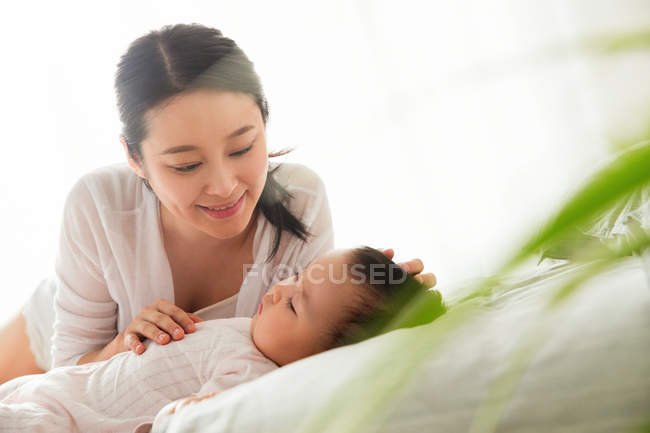 Happy young asian woman looking at her lovely baby sleeping on bed, selective focus — Stock Photo