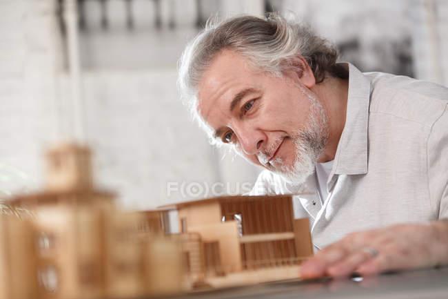 Nahaufnahme eines lächelnden professionellen Architekten, der mit einem Baumodell am Arbeitsplatz arbeitet — Stockfoto