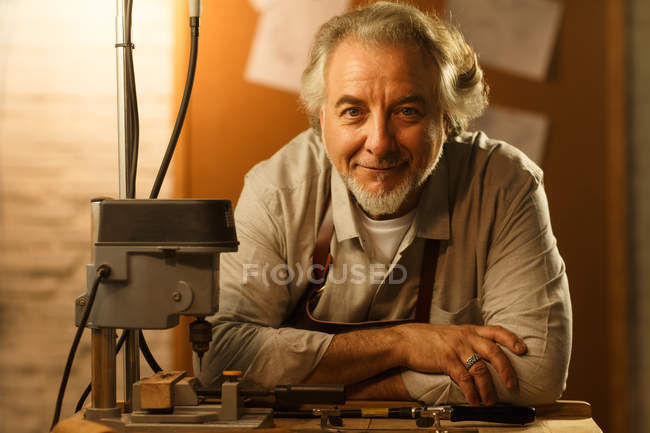 Professional mature jewelry designer sitting at workplace and smiling at camera — Foto stock