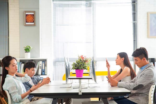 Vista lateral de hombres de negocios jóvenes aburridos y mujeres de negocios que usan smartphones en el lugar de trabajo - foto de stock