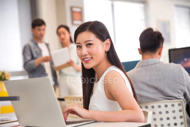 Bella felice giovane donna d'affari usign laptop e sorridente alla fotocamera mentre i colleghi che lavorano dietro in ufficio — Foto stock