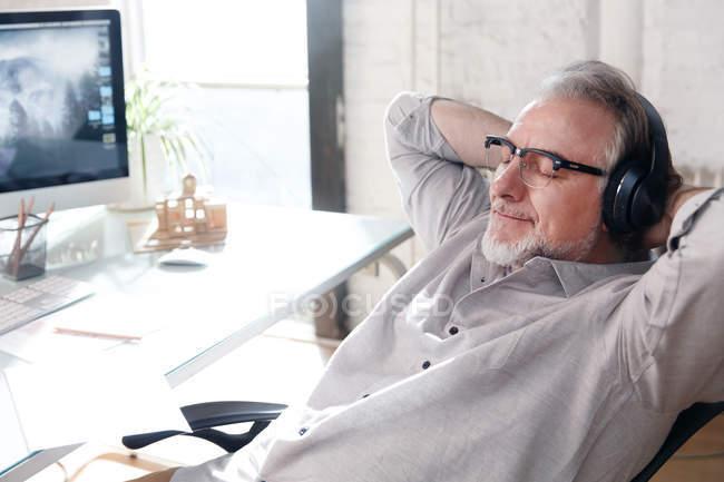 Rilassato architetto maturo in occhiali e cuffie seduto con le mani dietro la testa sul posto di lavoro — Foto stock