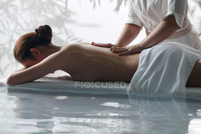 Side view of young woman receiving body massage in spa, cropped shot — Stock Photo