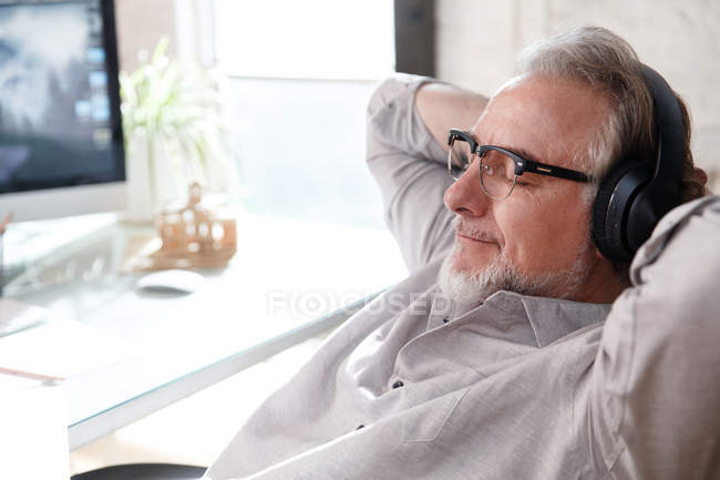 Relaxed mature architect in eyeglasses and headphones sitting with hands behind head at workplace — Stock Photo