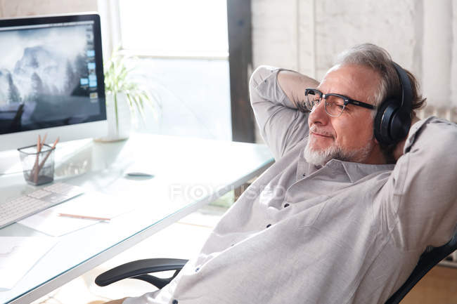 Smiling mature architect in eyeglasses and headphones sitting with hands behind head at workplace — Stock Photo
