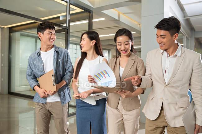 Souriant jeunes asiatiques entreprises collègues marcher et discuter de documents au bureau — Photo de stock
