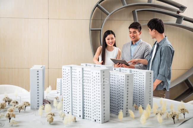 Улыбаясь профессиональных молодых азиатских архитекторов обсуждении проекта в офисе — стоковое фото