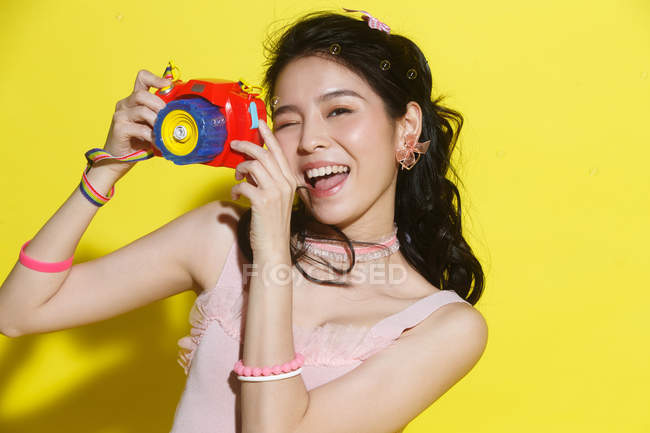 Attractive happy young asian woman holding colorful camera and smiling on yellow — Stock Photo