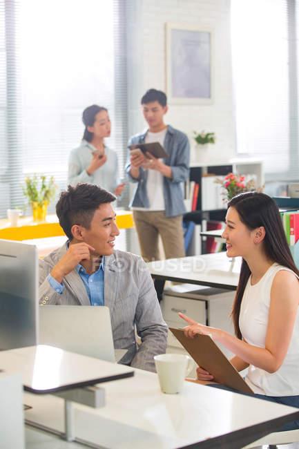 Sourire de jeunes collègues masculins et féminins, parler et regarder l'autre travail ar — Photo de stock