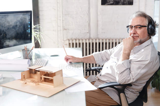 Professional mature architect in headphones working with new project and using desktop computer in office — Stock Photo