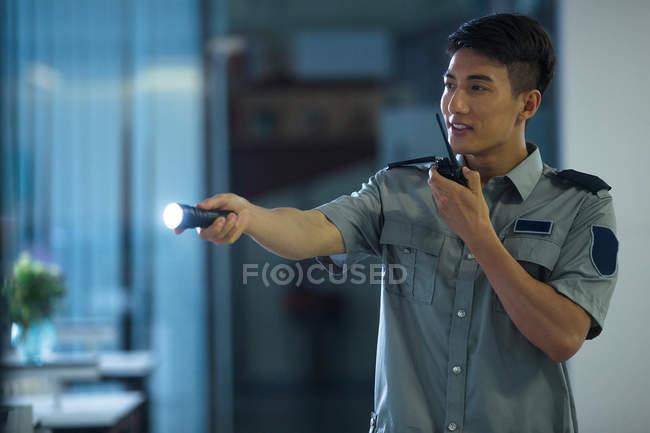 Улыбающийся молодой охранник Холдинг фонарик и использовать рацию в бизнес-центре ночью — стоковое фото
