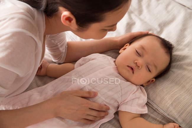 Обрезанный выстрел молодой матери, глядя на милый ребенок спит на кровати — стоковое фото