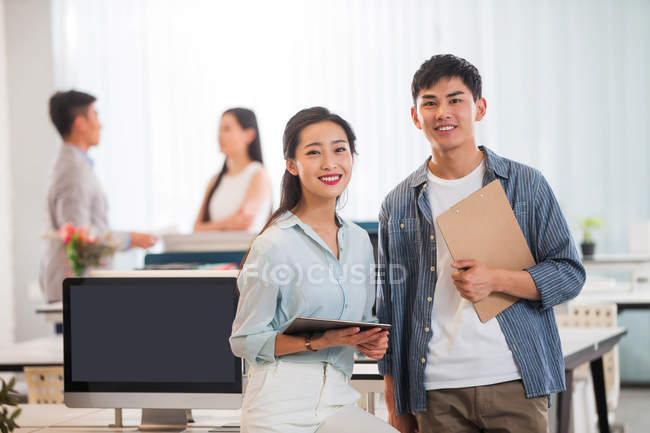 Happy young asian businessman and businesswoman with clipboard and digital tablet standing together and smiling at camera in office — Stock Photo