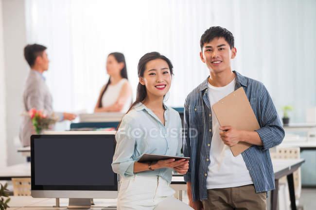 Щасливий молодий Азіатський бізнесмен і підприємець з буфера обміну і цифровий планшет стояли разом і посміхається на камеру в офісі — стокове фото
