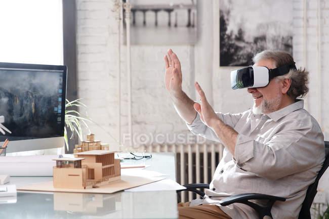 Smiling mature architect using virtual reality headset at workplace — Stock Photo