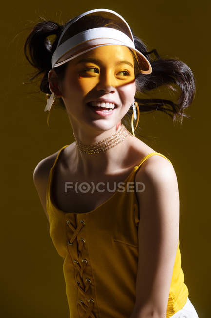 Beautiful happy young asian woman in cap and star-shaped earrings smiling and looking away in studio — Stock Photo