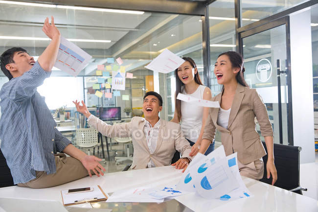 Excited young asian business colleagues throwing papers in modern office — Stock Photo