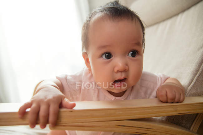 Close-up view of adorable asian infant baby with open mouth sitting in rocking chair at home — Stock Photo