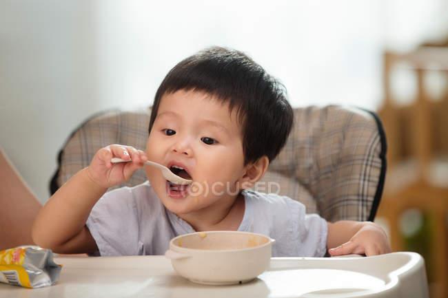 Entzückende asiatische Kleinkind mit Löffel und Essen zu Hause — Stockfoto