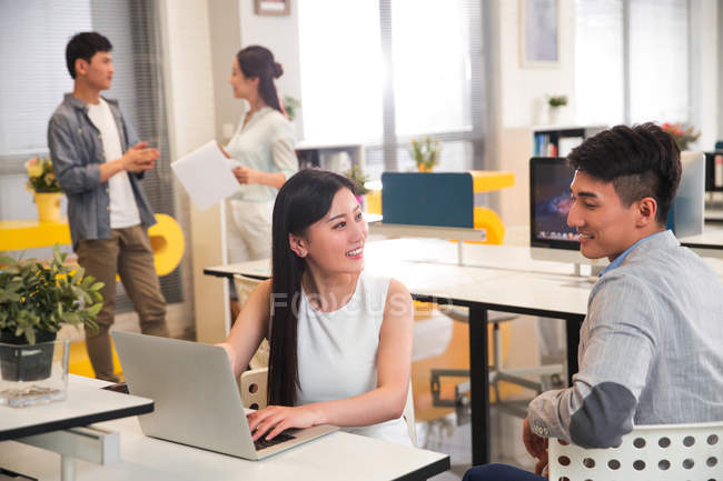 Smiling young professional asian business people working together in office — Stock Photo