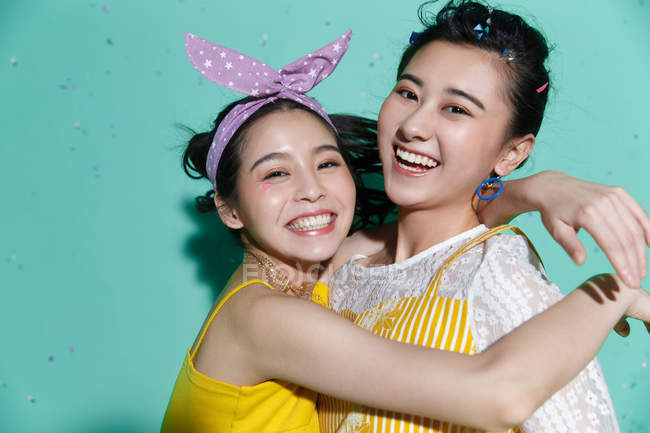 Beautiful happy asian girlfriends hugging and smiling at camera on blue — Stock Photo