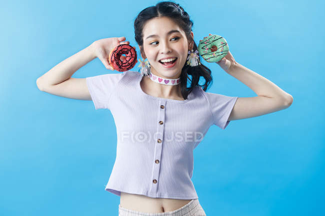 Beautiful happy young asian woman holding donuts isolated on blue background — Stock Photo
