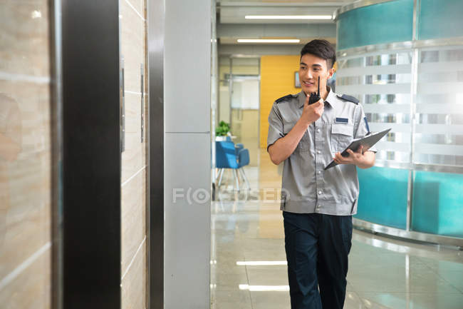Smiling young asian security guard holding clipboard and using walkie-talkie — Stock Photo