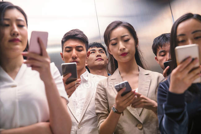 Serious young asian people using smartphones in elevator — Stock Photo