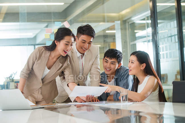 Улыбаясь молодых азиатских бизнесменов и предпринимателей, глядя на бумаге и обсуждению проекта в офисе — стоковое фото