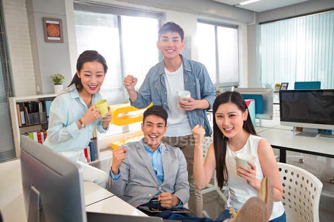 Счастливые молодые азиатские бизнес-команды, держа кубки и пожимая кулаками в современном офисе — стоковое фото