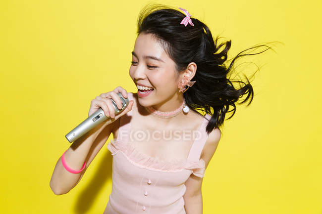 Beautiful happy young asian woman holding microphone and singing on yellow background — Stock Photo