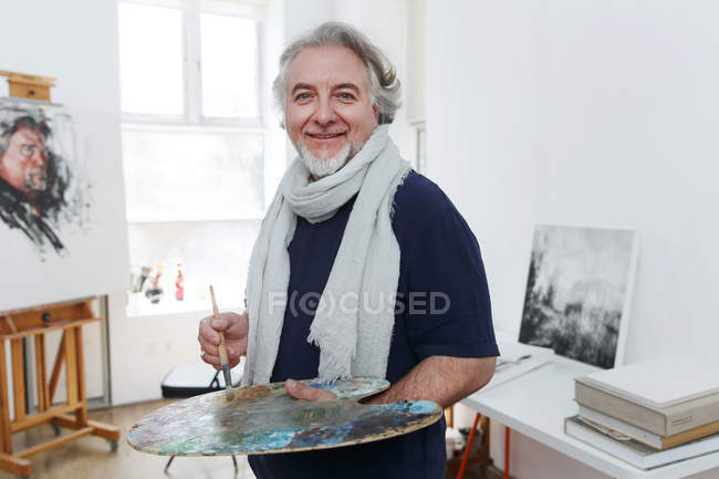 Handsome happy mature artist holding palette with brush and smiling at camera in studio — Stock Photo