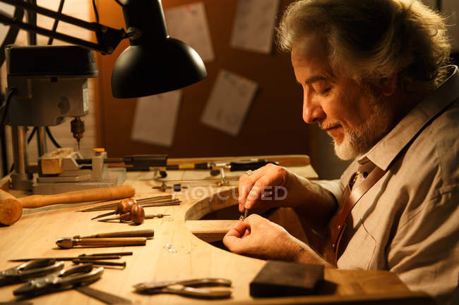 Profile view of professional jewelry designer working with tools and ring at workshop — Stock Photo