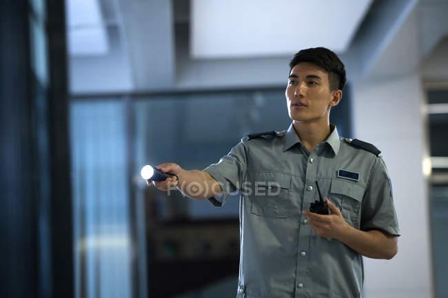 Jeune garde de sécurité asiatique tenant lampe de poche et talkie-walkie dans le bureau la nuit — Photo de stock