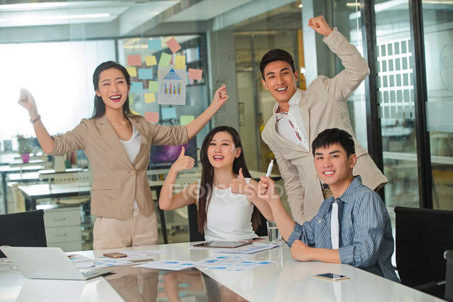 Excited young asian businessmen and businesswomen triumphing and showing thumbs up in modern office — Fotografia de Stock