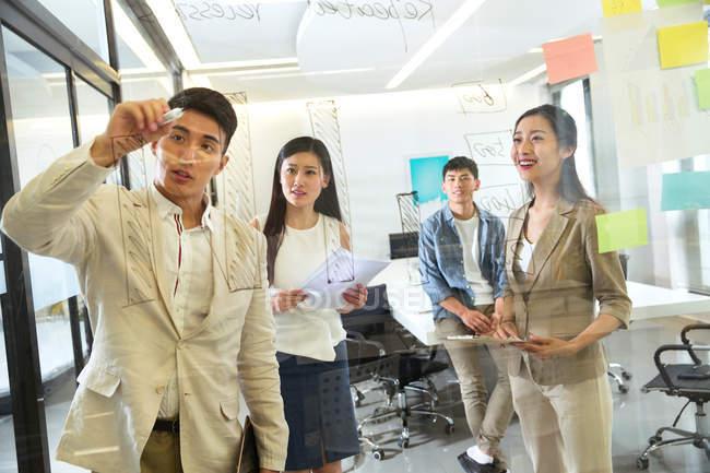 Vue à travers le verre de jeunes gens d'affaires asiatiques prendre des notes lors de la réunion au bureau — Photo de stock