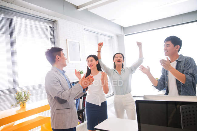 Happy young asian business team celebrating success and giving each other high five in modern office — Stock Photo