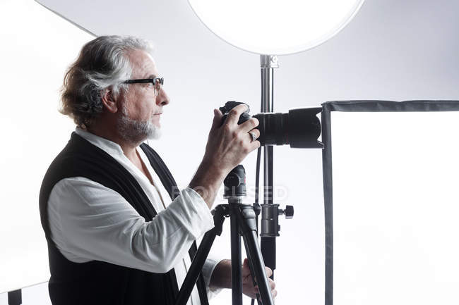 Side view of professional male photographer working with photo camera in studio — Stock Photo