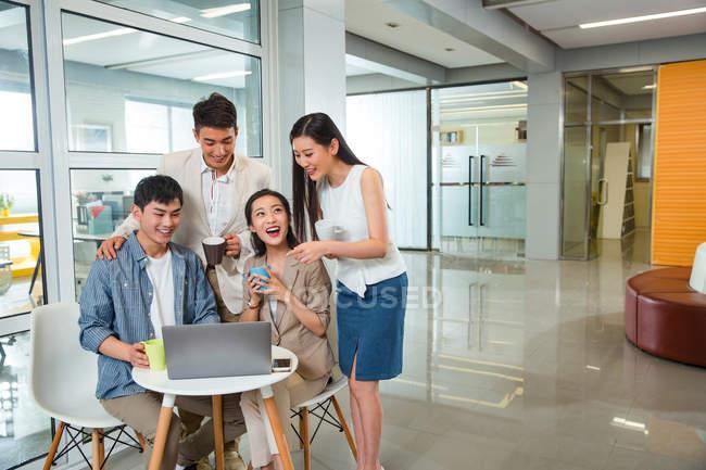 Felici giovani colleghi asiatici in possesso di tazze e utilizzando il computer portatile insieme durante la pausa caffè in ufficio — Foto stock