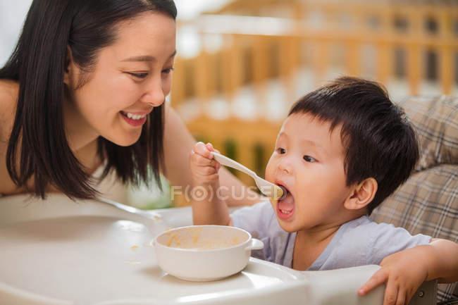 Glückliche junge asiatische Mutter blickend Baby hält Löffel und essen zu Hause — Stockfoto