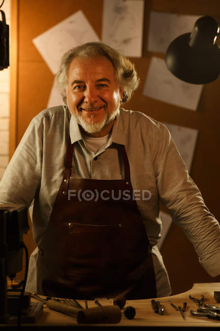 Professional happy mature jewelry designer in apron leaning at desk and smiling at camera in workshop — Stock Photo