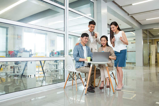 Улыбающиеся молодые профессиональные азиатские бизнесмены, работающие с ноутбуками и пьющие кофе вместе в офисе — стоковое фото