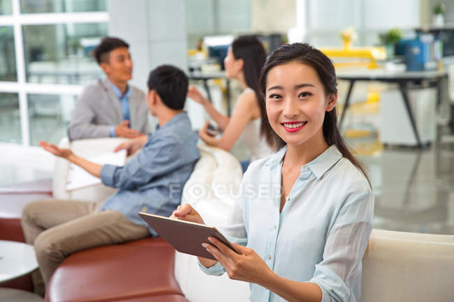 Beautiful young asian businesswoman using digital tablet and smiling at camera, colleagues talking behind in office — Stock Photo
