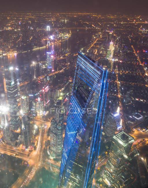 Vista aérea del majestuoso paisaje urbano de Shanghai con rascacielos y calles en la noche - foto de stock
