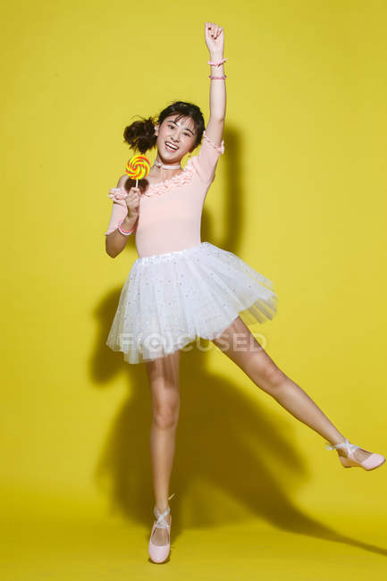 Full length view of beautiful happy asian girl in skirt holding colorful lollipop and smiling at camera on yellow background — Stock Photo