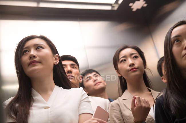Faible angle de vue des jeunes asiatiques graves debout ensemble dans l'ascenseur — Photo de stock