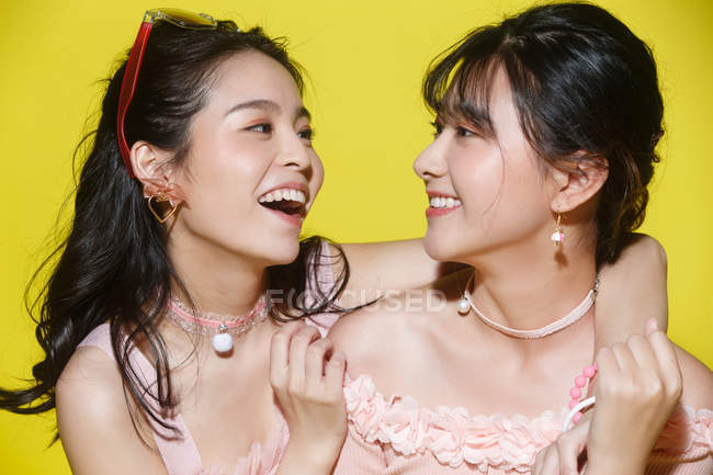 Beautiful happy stylish asian girls smiling each other isolated on yellow — Stock Photo