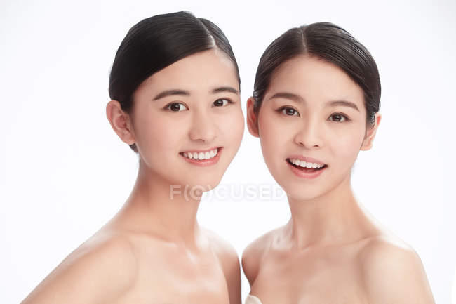 Beautiful happy young asian women smiling at camera isolated on white — Stock Photo