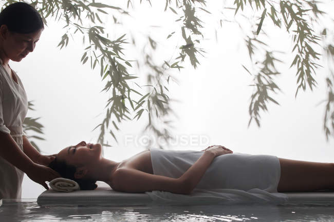 Side view of young asian woman receiving head massage in spa — Stock Photo